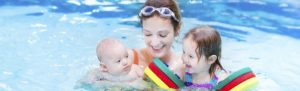 mother-having-fun-in-swimming-pool-with-two-kids-570x172_c